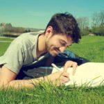 芝生で執筆する男性